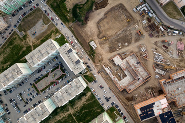 Aerial city view with crossroads, roads, houses, buildings, parks, parking lots, bridges. A large construction of multi-storey buildings with construction trucks, cranes and workers
