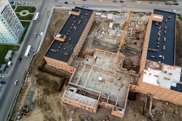 Aerial view:Construction of residential multi-storey houses made of bricks with the help of a construction crane in a new residential area of the city.