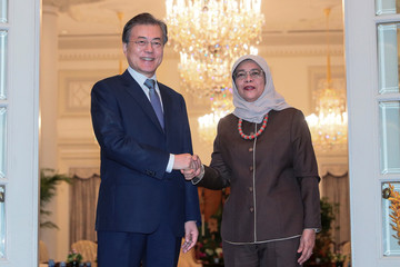 South KoreaÕs President Moon Jae-in shakes hands with SingaporeÕs President Halimah Yacob during a visit at the Istana in Singapore