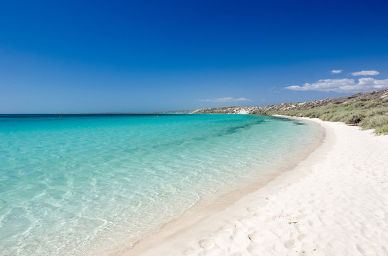 Stunning, white sand beach with turquoise, tropical sea under a clear, blue sky. Coral Bay, Western Australia, Australia.