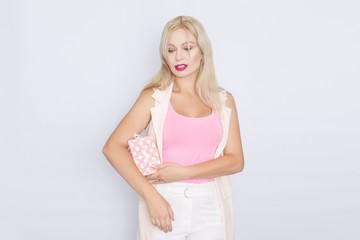 business portrait of a blond woman with bright make-up in a pink T-shirt and pink jacket on a white background. Holds a gift box in her hands