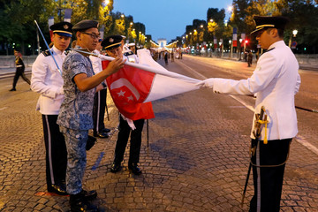 The Republic of Singapore Air Force soldiers attend a rehearsal of the Bastille day parade on the Champs-Elysees avenue in Paris