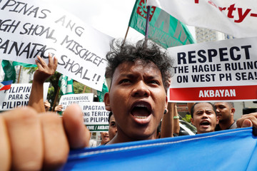 Members of the Akbayan activist group chant anti-China slogans as they march towards the Chinese consulate during a rally on the South China Sea dispute, in Makati, Metro Manila