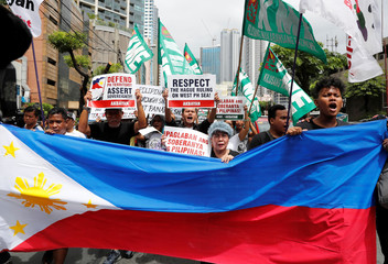 Members of the Akbayan activist group display a Philippine flag and chant as they march towards the Chinese consulate during a rally on the South China Sea dispute, in Makati, Metro Manila