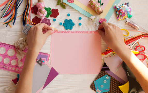 Woman's hand cut paper, scrapbooking for wedding or other festive decorations . Tools for scrapbooking.