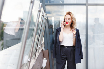 Portrait of a positive stylish charming successful businesswoman in formal suit talking on the phone with her husband