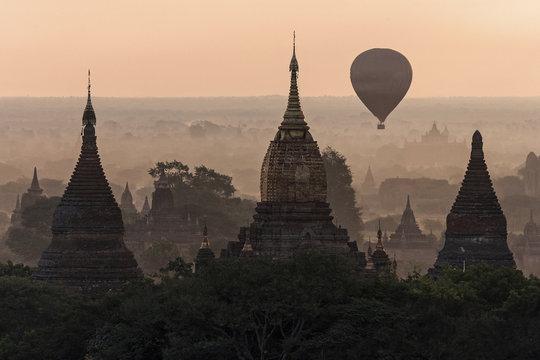 View of pagodas, temples, hot air balloon floating over pagodas field, sunrise, morning light, Bagan, Mandalay region, Myanmar, Asia