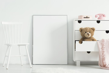 Mockup of white empty poster between chair and cabinet with teddy bear in kid's room interior. Real photo