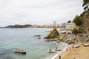 Lloret de Mar / Spain - June 27, 2018: Beach off the coast of Lloret de Mar, Costa Brava. People on the beach lie on sun loungers under umbrellas. Resting under a castle on the beach in the city.