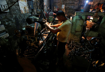 A worker operates a lathe as he makes spare parts of car gearboxes at a workshop in Kolkata