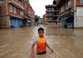 A boy walks along the flooded neighborhood after incessant rainfall in Bhaktapur