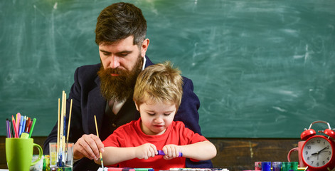 Art lesson at kindergarten. Teacher helping the boy to create picture. Man painting with long brush while kid opens the marker.