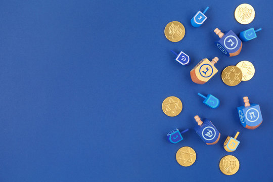 Dark blue background with multicolor dreidels and chocolate coins. Hanukkah and judaic holiday concept.
