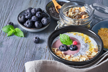 Yogurt with muesli, blueberries, poppy seeds, mint and crushed cornflakes served in black shiny bowl