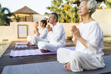 Senior adults practicing yoga outdoors