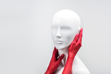 cropped image of woman in red paint touching mannequin neck and face isolated on white
