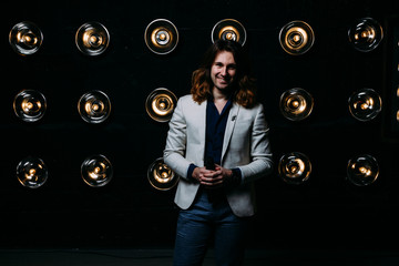 a man in a white jacket and in a black shirt, with long hair, stands against the backdrop of bright lanterns, safites. on the stage.performance. smiles