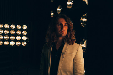 a man in a white jacket and in a black shirt, with long hair, stands against the backdrop of bright lanterns, safites. on the stage.performance