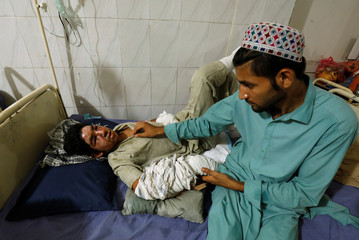 Relative sits with an injured boy, who survived Tuesday's suicide attack in Peshawar