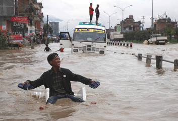 A boy smiles as he uses an improvised raft to maneuver through the floodwater after incessant rainfall in Bhaktapur
