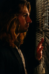 a man with long hair is standing near the window, opening the blinds with lobes, in a black jacket. look at the street, spy on people,sunrise