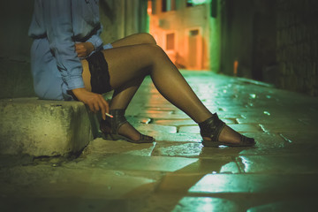 Prostitute with cigarette working on the night street.
