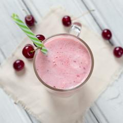 Milkshake or cherry smoothie on white wooden table. Wholesome breakfast