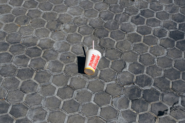 Minimalistic picture of a cardboard grass of a junk drink from a fast food company discarded and forgotten on the street.