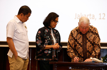 Freeport-McMoRan Chief Executive Officer Richard Adkerson signs an initial agreement for the state-owned mining company PT Inalum to take a controlling stake in Freeport's local unit during a ceremony in Jakarta