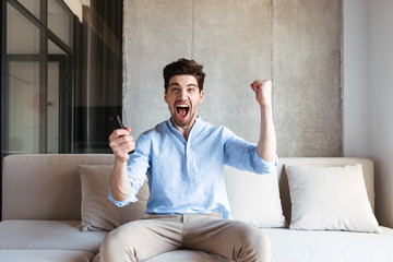 Happy young man holding TV remote