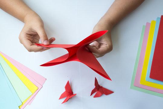 Детские руки делают бабочку оригами из красного листика бумаги на белом фоне. Обучение детей