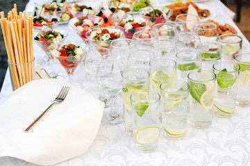 Catering for outdoors party. Catering buffet food on some festive event, party or wedding reception. Water with lemon and mint. Greek salad in glasses on table, banquet food. Catering service.