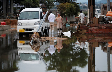 Local residents stand in a flooded area in Mabi town in Kurashiki