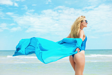 A beautiful young girl with light hair in a blue swimsuit and a blue chiffon beach dressing gown relax on beach in the sea in sunny hot day