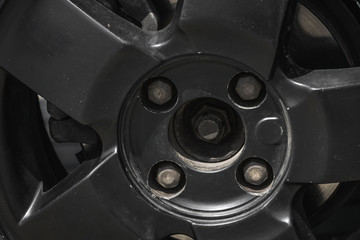 black wheel of a car with four bolts and brakes behind it