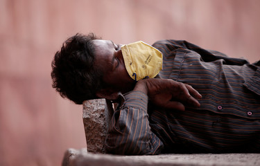 A rickshaw puller wearing a mask sleeps on pavement at a roadside in the old quarters of Delhi