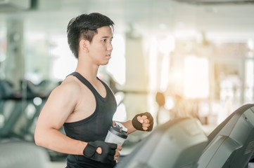 Young man in sportswear running on treadmill at gym.sport, fitness, lifestyle, technology and people concept - smiling men exercising on treadmill in gym.