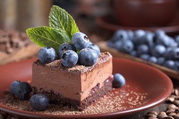 Chocolate cake with blueberries and mint .