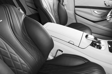 Modern Luxury car inside. Interior of prestige modern car. Comfortable leather seats. Red perforated leather cockpit. Modern car interior details. Black and white