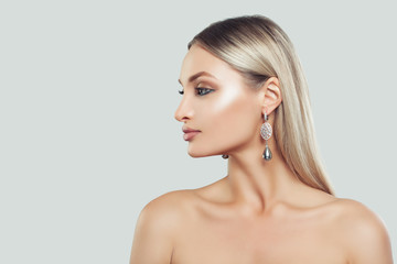 Beautiful Woman Face Closeup. Woman with Perfect Makeup and Pearls Earrings on White Background