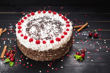 Sweet white cake with cream and cherry on the black background