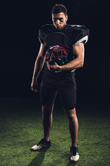 serious american football player in black uniform holding helmet and looking at camera on black