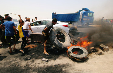 Iraqi protesters burn tires and block the road at the entrance to the city of Basra