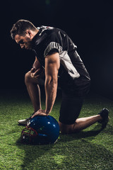 young serious american football player standing on one knee on grass with helmet on black