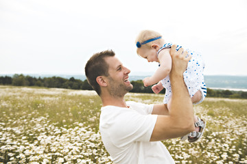 little baby girl and his father enjoying outdoors in field of daisy flowers