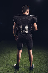 rear view of american football player in black uniform standing on grass on black