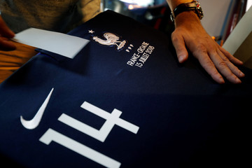 An employee displays an official France team soccer jersey at NSH Foot Store in Paris