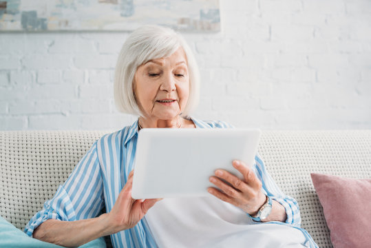 portrait of senior woman using tablet on sofa at home