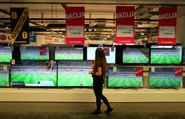 A woman looks at televisions in a store in Zagreb