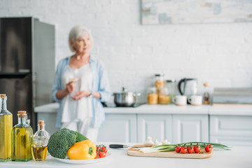 selective focus of fresh vegetables on counter and senior woman with glass of wine standing at stove in kitchen